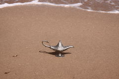 Magic lamp on a sand. Silver magic lamp on a sand and sea background stock photo