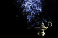 Magic lamp from the story of Aladdin with Genie appearing in blue smoke concept for wishing, luck and magic Stock Images