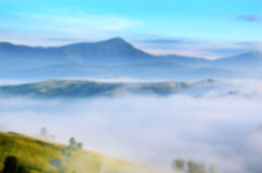 Magic landscape at sunrise in the mountains in the fog. Backgrou Stock Photo