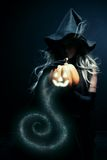 Magic light. Pretty witch holding pumpkin over dark background Royalty Free Stock Photography