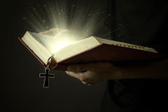Magic light of holy bible. Hands of man holding holy bible and wooden rosary with magical rays Stock Photography
