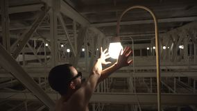 The magic of light. Naked man in sunglasses admires light bulbs stock footage