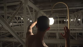 The magic of light. Unclothed man in sunglasses admires light bulbs stock footage