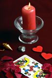 Magic and love. Various esoteric objects, candle, rose petals and two heart shapes Royalty Free Stock Image