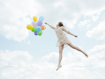 Magic lovely girl flying in the sky with balloons Stock Photo