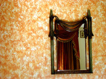 Magic Mirror. A beautiful antique mirror on an orange wallpapered wall Royalty Free Stock Images