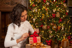 Magic moment of Christmas. Girl opens gifts Royalty Free Stock Photography