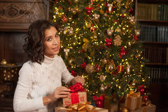 Magic moment of Christmas. Girl opens surprise gift for Christma Royalty Free Stock Photos