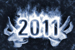 Magic New Year 2011. Happy New Year background with effect of cast magic spell, blue energy flames wrapping around digits 2011 in the dark glowing between hands Stock Photo