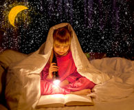Magic nigh,young girl reading a book in the dark, with a flashli Royalty Free Stock Photo