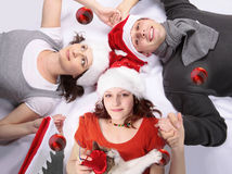Magic night. Teenager girl holding mother and father's hands in a circle with Christmas hats Royalty Free Stock Images