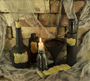 Magic objects on stone background. Magic bottles with burning candles and cup of blood on stone background Royalty Free Stock Image