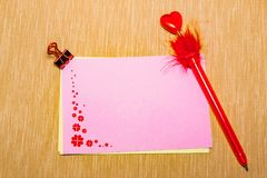 Magic pen and paper note with red flowers and paperclip on yellow background, minimal concept and similarities differences.  Royalty Free Stock Images