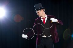 Magic, performance, circus, show concept - magician in top hat showing trick with linking rings Stock Photo