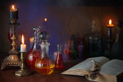 Magic potion, ancient books and candles. On dark background royalty free stock images