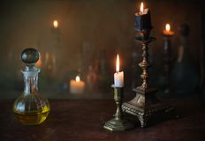 Magic potion, ancient books and candles. On dark background Royalty Free Stock Image