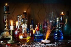 Magic potion, ancient books and candles. On dark background Stock Images