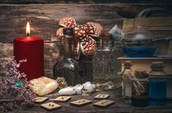 Witchcraft. Paranormal table of magician. Magic potion, runes for divination and stack of old books on the magician table. Witchcraft concept stock photos