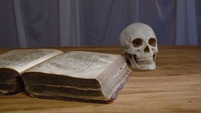 The magic rite. Ancient book and human skull. Concept for Halloween stock video footage