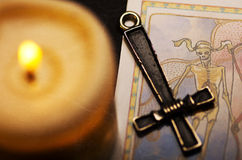 The magic ritual. Inverted cross, tarot card and candle Stock Image