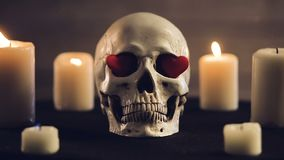 Magic ritual with skull and hearts. Magic rite.A human skull and burning candles. Hearts are inserted into the eye sockets of the skull. The candles are stock footage