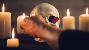 Magic ritual with skull and hearts. Magic rite.A human skull and burning candles. Male hands insert hearts into the eye sockets of the skull. Concept for stock video footage