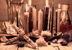 Vintage still life with cross, black candles, minerals and flasks on table. Magic ritual. Wicca, esoteric and occult background with vintage witch objects royalty free stock image