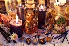 Magic runes, black candles, flowers and berries on witch table in candle light. Occult, esoteric, divination and wicca concept. Alternative medicine and royalty free stock images