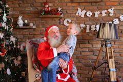 Magic Santa Claus and little boy fooling around and have fun tog Royalty Free Stock Photos