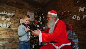 Magic Santa gives small boy for Christmas coveted gift in cozy room with big tree. Enthusiastic male child rejoices and from virtual reality glasses that father stock video footage