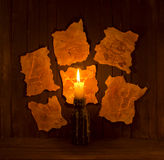 Magic signs with candle. Six magic symbols on scraps of paper with candle Royalty Free Stock Image
