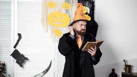 Magic, spell, book of magic. Bearded magician reads old book about magic. Halloween Wizard. Bearded man in Halloween stock video footage