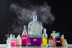 Magic spells in antique bottles. Over black background and smoke Stock Images