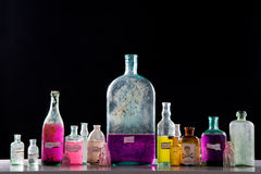 Magic spells in antique bottles. Over black background Royalty Free Stock Image