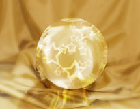 Magic star sphere. Magic star crystal ball on a gold fabric background Royalty Free Stock Photos