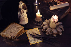 Magic still life with skull and the tarot cards. Halloween and magic still life with evil candles, books, skull and the tarot cards. Fortune telling seance or royalty free stock photography