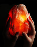 Magic stone. A yellowish red stone light from inside held by two hands Stock Photo