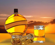 Magic sunset in bottle & glass of wiskey. Royalty Free Stock Photos