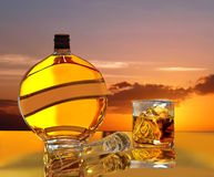 Magic sunset, sunrise in bottle & glass of wiskey. Stock Photo