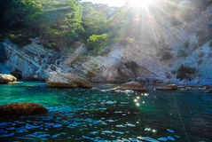 Magic sunshine through the mountains in the blue bay in the Mediterranean Sea Royalty Free Stock Images