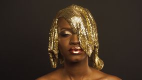 Magic surreal golden african american female model with bright glitter makeup and glossy golden hairstyle.  stock video