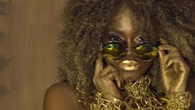Magic surreal golden african american female model in massive sunglasses with bright glitter makeup, glossy golden. Hairstyle and big red lips posing on the stock video
