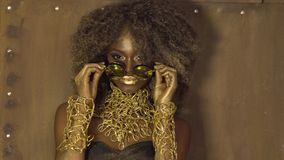 Magic surreal golden african american female model in massive sunglasses with bright glitter makeup, glossy golden. Hairstyle and big red lips stock video