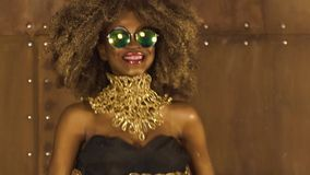 Magic surreal golden african american female model in massive sunglasses with bright glitter makeup, glossy golden. Hairstyle and big red lips posing and stock footage