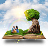 Magic tree love. Young couple sitting on the grass near the magic tree of love Royalty Free Stock Images