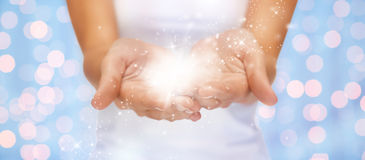 Magic twinkles or fairy dust on female hands Stock Photo