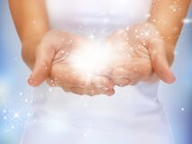 Magic twinkles on female hands. Bright closeup picture of magic twinkles on female hands stock photo