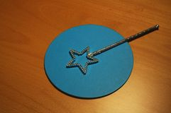 Magic wand. Toy magic wand on a blue circle (on wood table Royalty Free Stock Photo