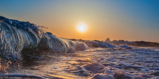 Magic wave splash close-up, at sunset. In Portugal, Algarve area. Royalty Free Stock Photography
