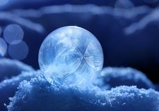 Magic of winter,. Frozen soap bubble ball on snow, crystal formations, dark blue background royalty free stock image
